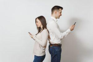 Man and woman texting facing away