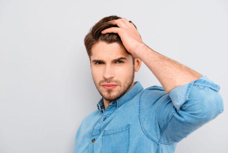 Man running fingers through hair