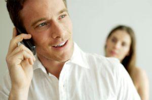 Man talking on phone woman behind
