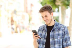 Man texting smiling