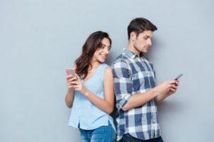 Man texting woman behind