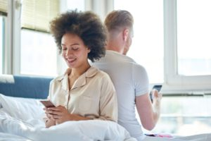 Woman and man texting backs to each other