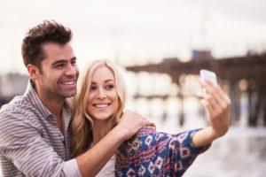 Woman taking selfie with man