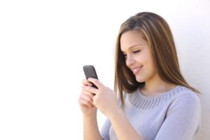 Woman texting smiling