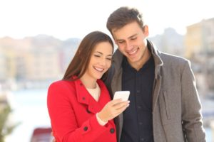 Woman texting with man smiling